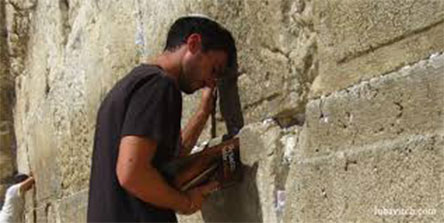 Man praying against wall