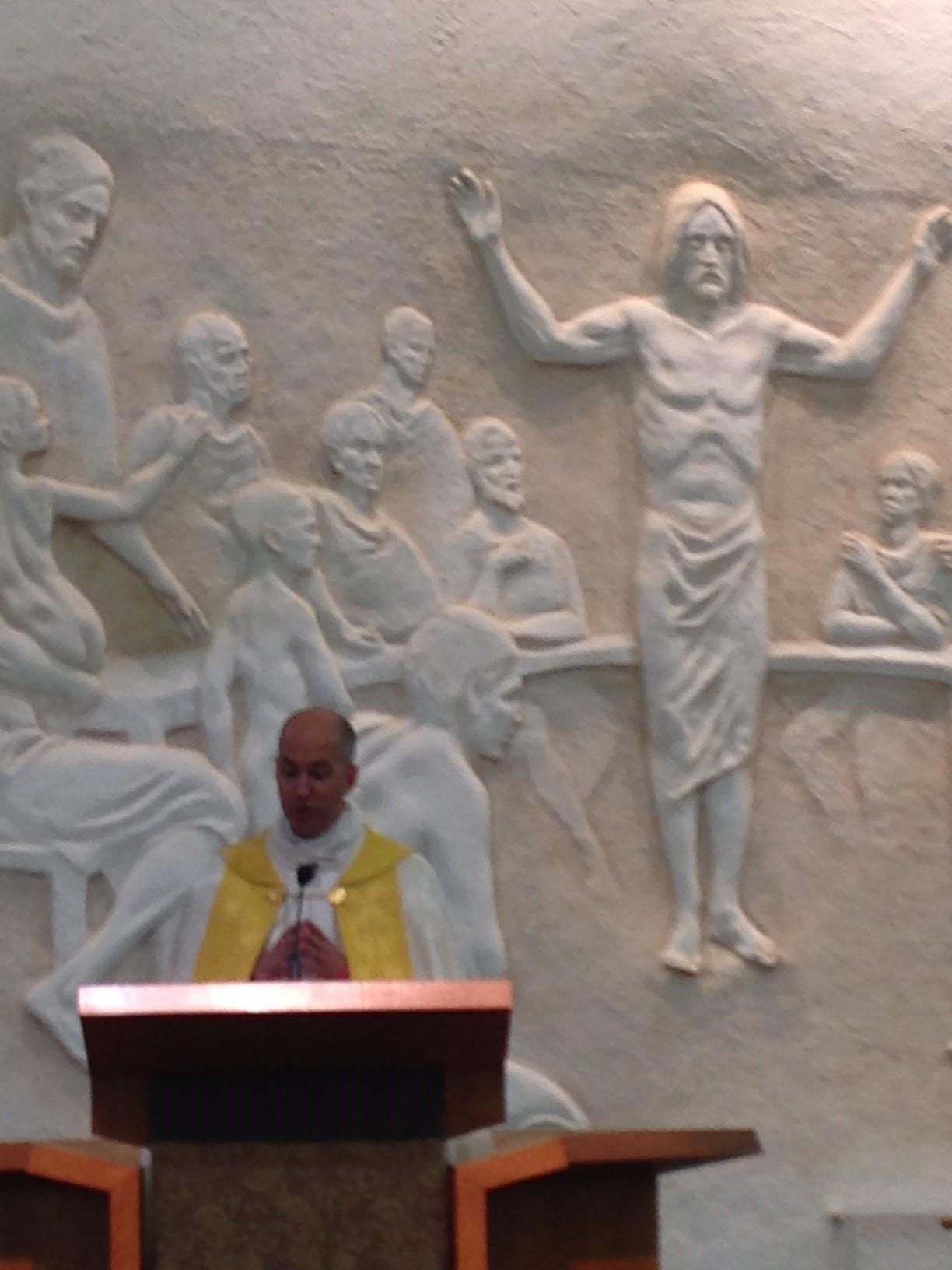 Priest speaking in front of mural